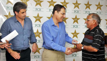 Chief guest Mr. Shafqat Naghmi presents a cheque to retiring umpire Nazir jnr