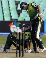 Misbah-ul-Haq helps out his teammates Kamran Akmal